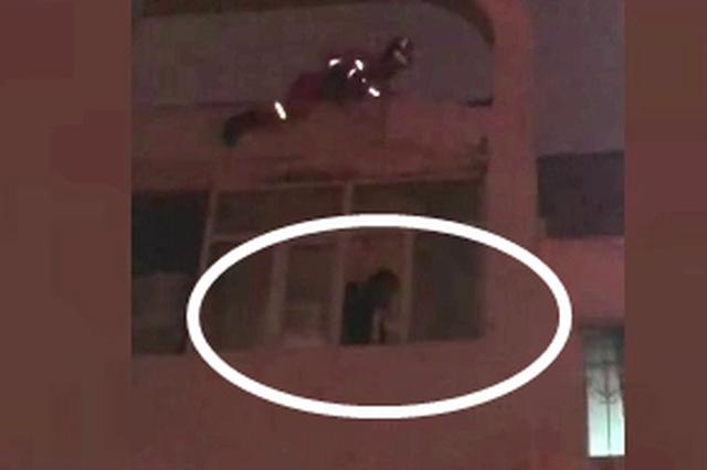 惊险!哈尔滨一女孩欲跳楼被消防员从天而降推进屋