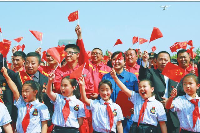 庆祝新中国成立70周年 大庆举行佩戴国旗徽章活动