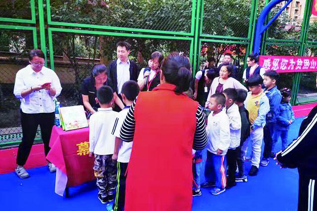 哈市四季上东物业公司为业主放露天电影为山区儿童捐书