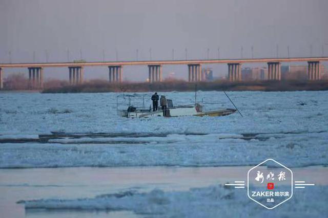 又有漁船被困江上冰排中,船上兩人持長木桿自救上岸