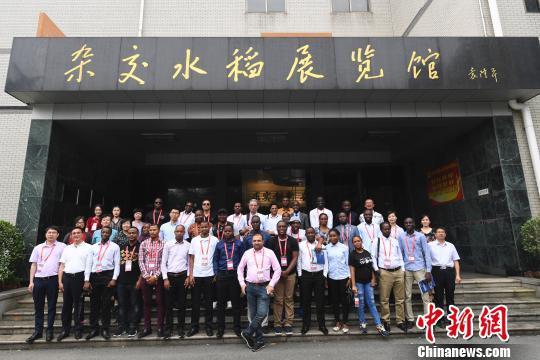 非洲记者与工作人员在杂交水稻展览馆前合影。 杨华峰 摄