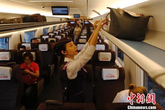 动车组列车员正在检查旅客行李摆放位置。 殷立勤 摄