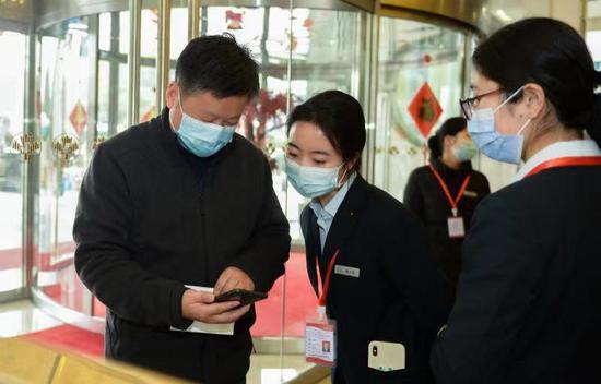 1 月 16 日,长沙市政协委员陆续赶到驻地报到,报到前出示健康码与行程码。图 / 记者吴琳红