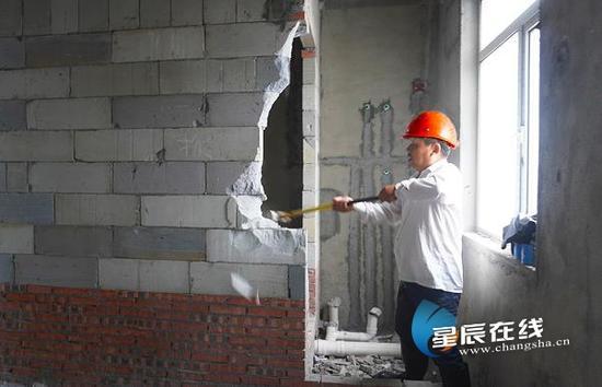 (施工人员正在对违规改造房屋景进行拆除。通讯员供图)