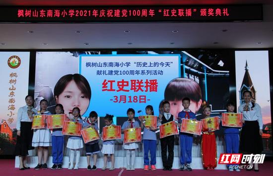 """枫树山东南海小学校长与书记为获得红史联播""""十佳作品""""的同学颁发奖杯与证书。"""