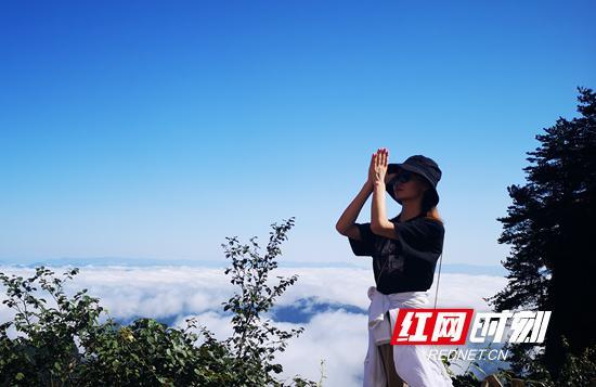 8月26日,一名游人在武陵源天子山游玩,壮丽的云海景不雅观让她陶醉不已。(吴勇兵 摄)