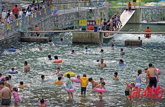 (8月18日,新邵县坪上镇清水村,当地村民和游客在戏水游玩。湖南日报·华声在线记者 李健 摄)
