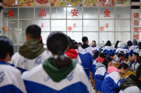 """12月4日,高一高二学生在桃源一中""""大食堂""""五元区排队买饭。新华社 图"""