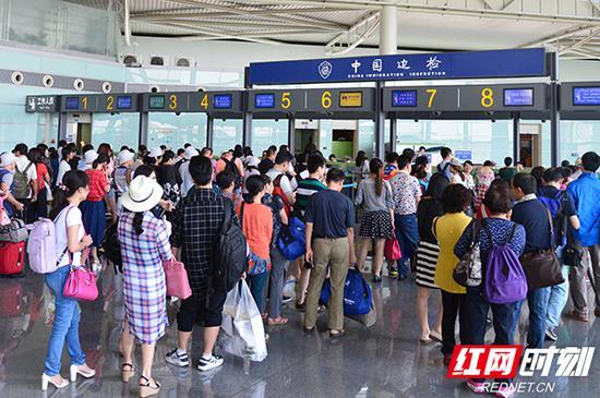 清明期间在长沙边检站排队候检的旅客。