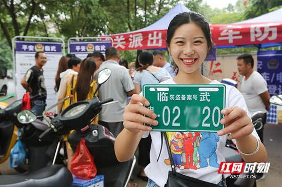 一市民高兴地领回了心仪的备案车牌号。