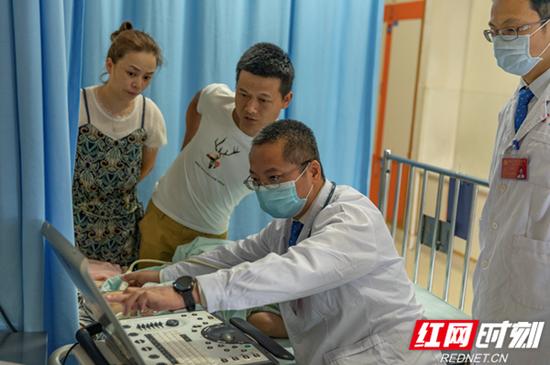 湖南省儿童医院心血管内科主任医师陈智正在给子毅做床旁彩超。