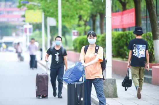 返校的学生拖着行李箱走在回宿舍的路上。