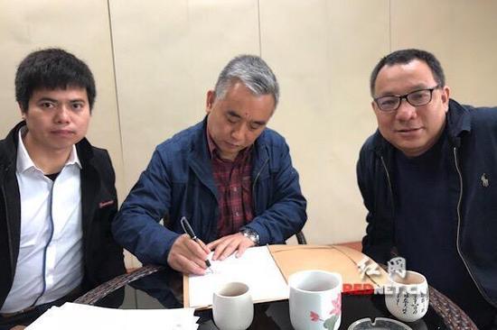 王跃文(中)与胡勇平(右)、刘凯(中)律师签署授权维权委托书。