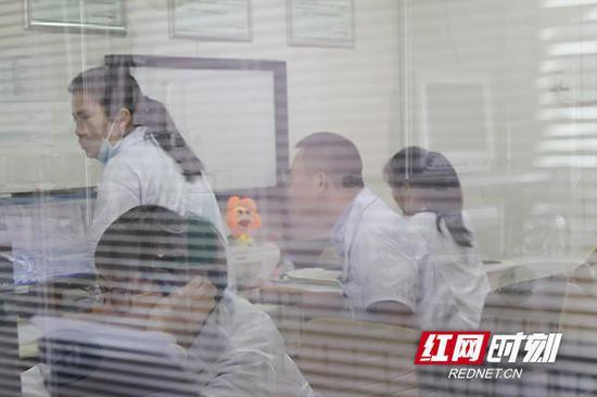 湖南省人民医院儿童医学中心的儿科医生在办公室忙碌着。