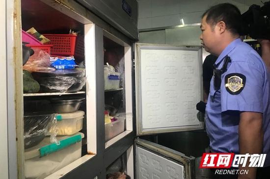 执法人员检查青舍饭庄的冰箱。