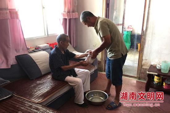 周仁南(右一)给已故妻子前夫的父亲擦手。图片来源:湖南文明网