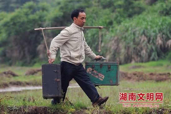 马恭志挑着电影放映机下乡。图片来源:湖南文明网
