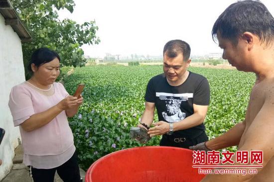 王国顺(中)指导养殖户规范养殖标准。图片来源:湖南文明网