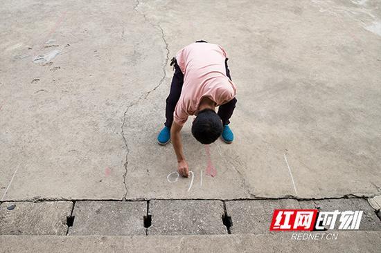开学典礼前,张利军在教学楼前的空地上用粉笔划分出各个班级的位置。