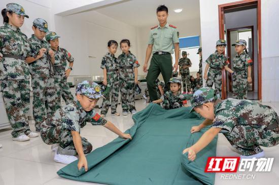 夏令营学员在教官的带领下学习了军被的折叠,并分组进行了竞赛。
