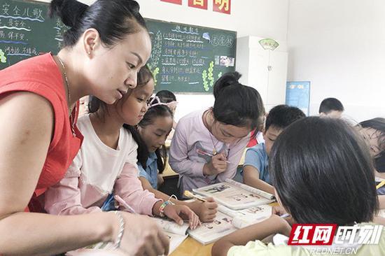 周琴在班上辅导学生学习。