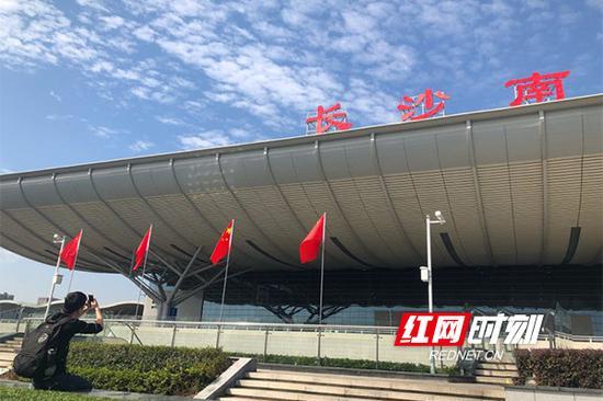 """一位旅客正在国旗下以""""长沙南""""三个字为背景,拍照留念。"""