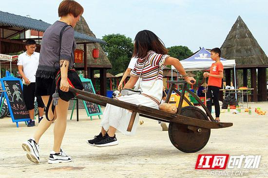 游客在景区体验童年游戏。