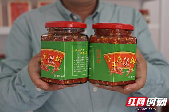潘建中举起已经装瓶的手工剁辣椒。
