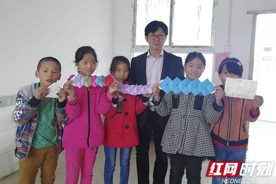 教师节,学生们把自己的手工制品送给张老师,张老师很开心。