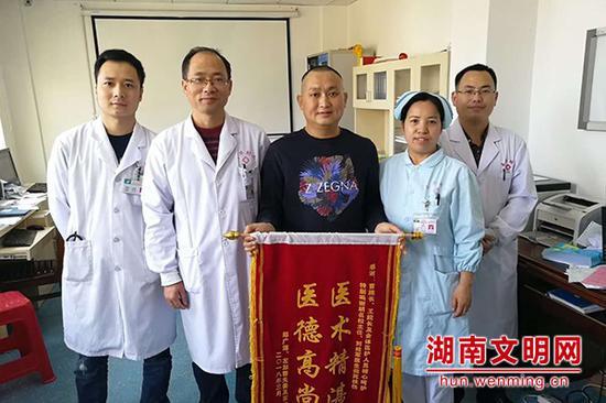 患者送来锦旗感谢胡军(右一)。图片来源:湖南文明网