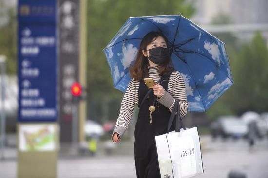 11月6日,长沙岳麓区梅溪湖路,出行的市民打着伞戴着口罩。图/记者谢长贵