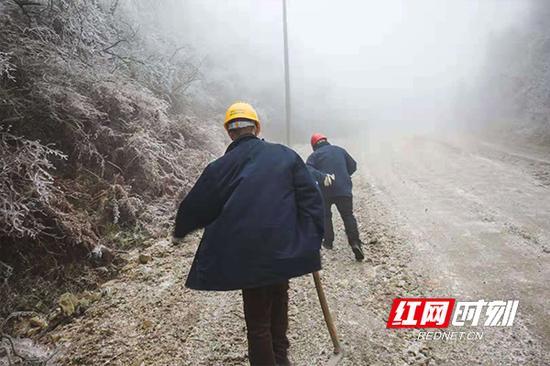 风雪中前行的电力巡线人。