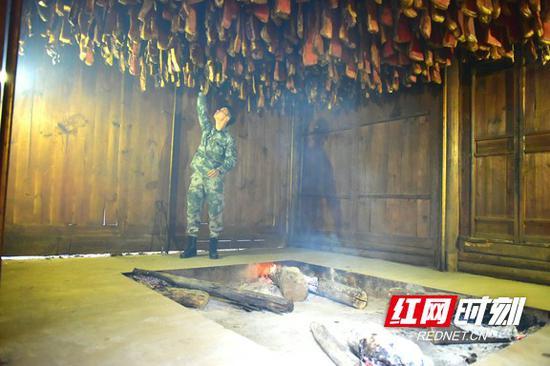 吴勇在木房子里查看腊肉熏制情况。