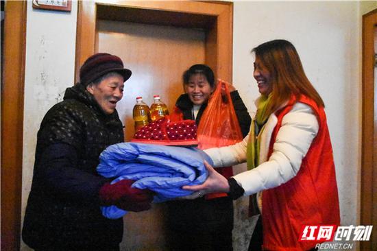 曾利萍和何秋兰带着生活物资来看望邓荣华老人。
