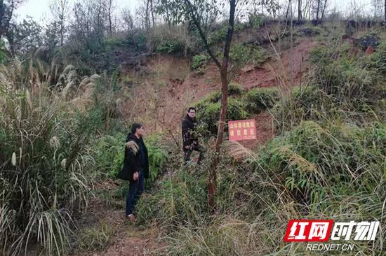 道县梅花镇政府工作人员到地质滑坡点巡查。