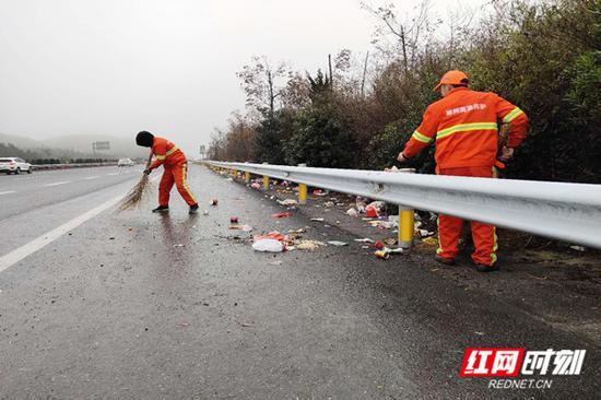 春运期间,许广高速郴州境内,养护工人正常清理路肩上的垃圾。