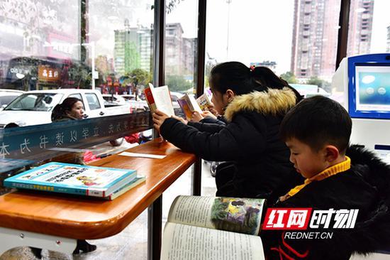3月9日,蓝山县三蓝广场24小时自助图书馆,孩子们在认真读书。