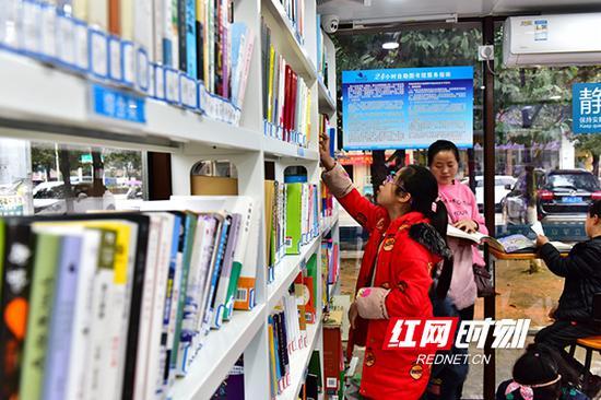 3月9日,蓝山县三蓝广场24小时自助图书馆,孩子在借阅图书。