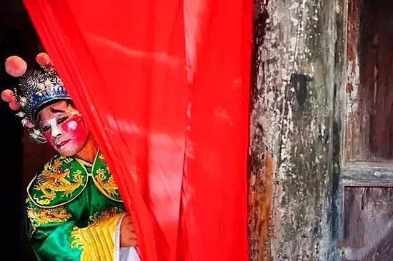 庙下村古戏台,一名桂阳湘剧演员掀起幕布一角观看台上演员的表演。图|郭立亮