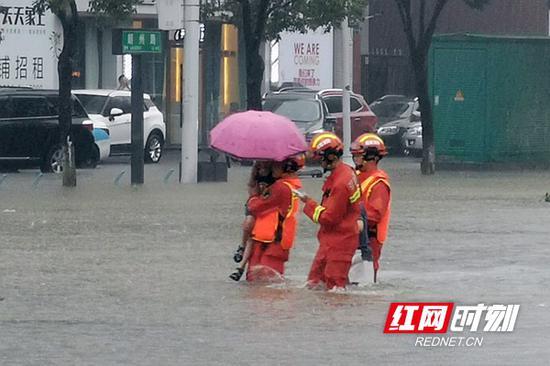 消防人员在大雨中帮助小孩过马路。