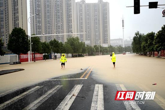 暴雨中,常德交警坚守在一线指挥交通。