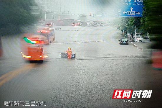 大雨中,市政工人现场看守危险地带,防止车辆进入。