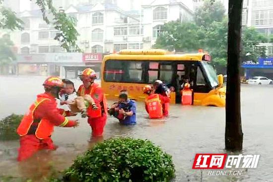 校车因积水不能通行,消防人员连成安全通道,护送孩子安全。