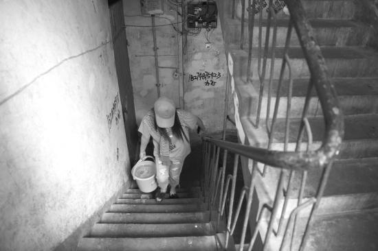 8月1日,南沙井巷某宿舍停水10多天,彭女士只能每天去附近的公共厕所提水生活。图/记者杨旭