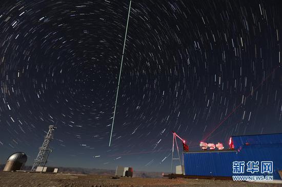 """在西藏阿里观测站,""""墨子号""""量子科学实验卫星过境,科研人员在做实验(2016年12月10日摄,合成照片)。 新华社记者 金立旺 摄"""