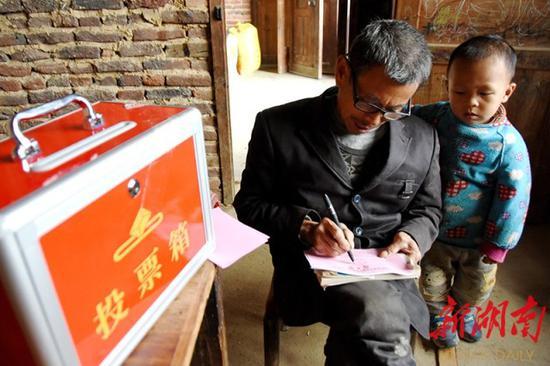 ↑2016年10月25日,双峰县井字镇三石村选区,选民在流动票箱前认真填写选票。当年10月24日至29日,该县开始进行县乡人大代表换届选举,选出新一届县级人大代表300余名和乡镇人大代表1200名。(资料图片)李建新 摄