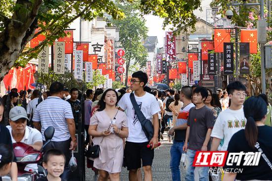 国庆首日,古色古香的太平老街装扮一新,整条街的商铺都插满了国旗。