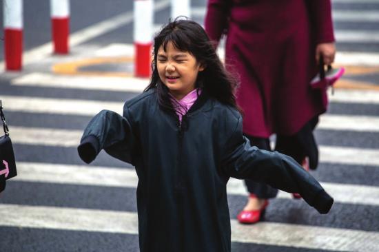 10月6日,长沙市湘江中路和解放西路路口,受冷空气影响,长沙气温持续下降,不少孩子穿上了大人的衣服来保暖。图/实习记者张云峰