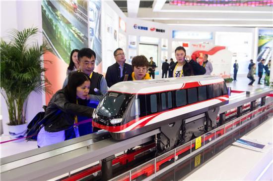 10月18日,观众在2019中国国际轨道交通和装备制造产业博览会上观看轨道交通产品模型。新华社发(陈思汗 摄)
