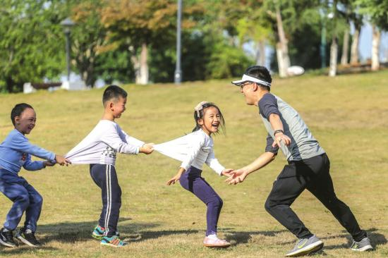"""10月20日,长沙天气晴朗,市民带着孩子在松雅湖旁玩""""老鹰捉小鸡""""的游戏。图/实习记者张云峰"""